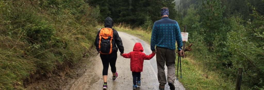 photo of couple hiking holding hands with child
