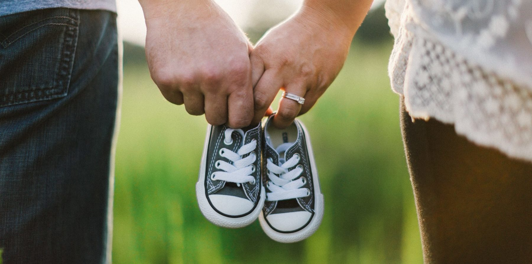 photo of couple holding baby shoes